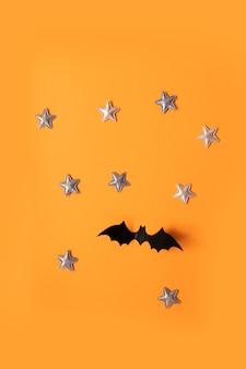 Halloween plat lag samenstelling van zwarte papieren vleermuizen vliegen omhoog en gouden sterren op een oranje achtergrond, bovenaanzicht.