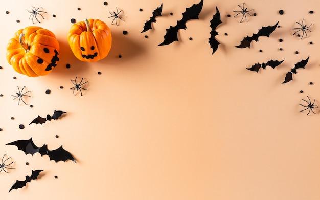 Halloween plat met decoraties gemaakt van pompoen, papieren vleermuizen en zwarte spin