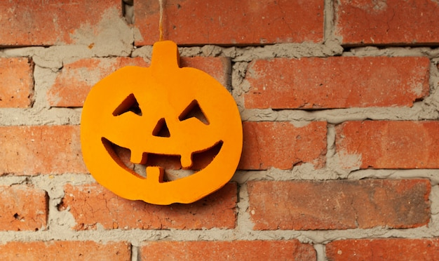 Halloween-pompoen dichte omhooggaand op de bakstenen muurachtergrond