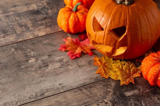 Halloween pompoen en herfstbladeren op houten tafel