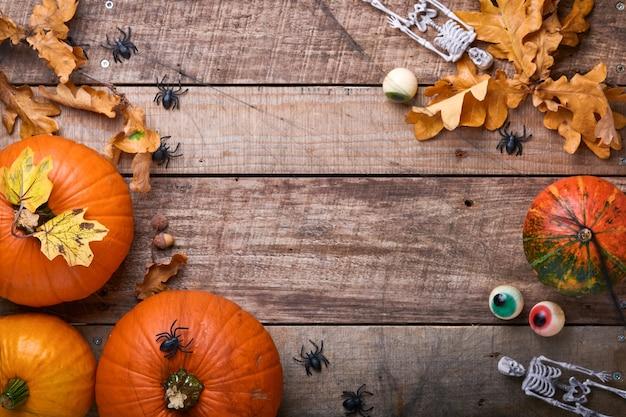 Halloween-pompoen. feestelijk herfstdecor van pompoenen, bladeren, spin, skeletten en grappige ogen op oude houten achtergrond. platliggende herfstcompositie met kopieerruimte.