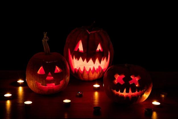 Halloween pompoen hoofd jack-o-lantern met enge kwade gezichten en kaarsen. seizoensgebonden verlichte decoratie. ziet er eng, kleurrijk neonlicht en donkere achtergrond uit. vakantie. zwarte vrijdag, verkoop.