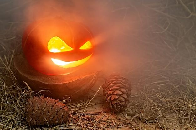Halloween-pompoen in rook staat in hooi op een houten standaard in de buurt van boskegels