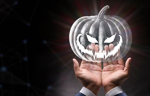 Halloween-pompoen in tot een kom gevormde handen op onscherpe donkere achtergrond happy halloween-concept