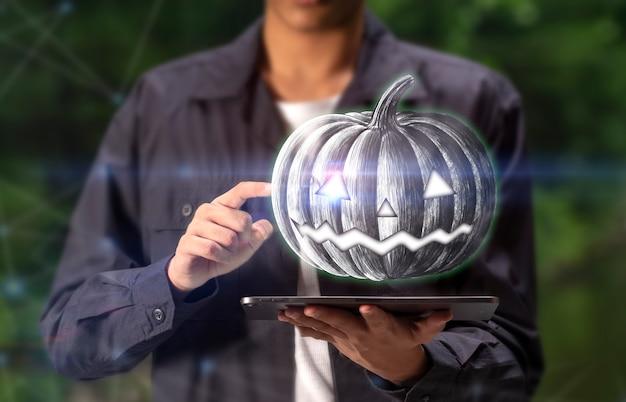 Halloween-pompoen in tot een kom gevormde handen op tablet voor gelukkig halloween-concept