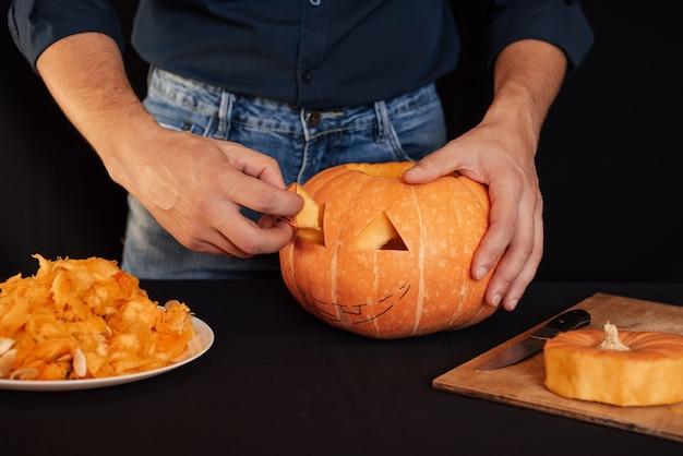 Halloween-pompoen. man handen bereidt traditionele decoratie voor de viering