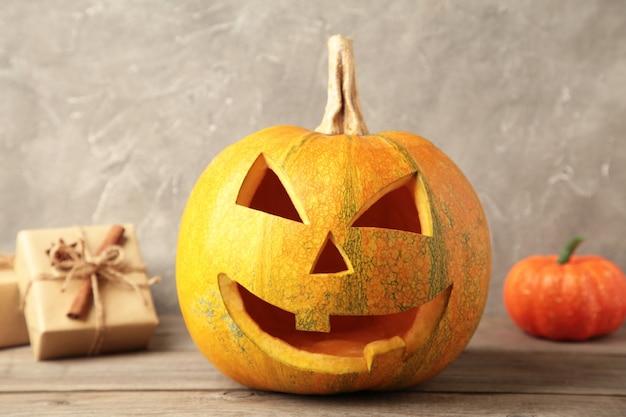 Halloween-pompoen met giften op grijze achtergrond. bovenaanzicht