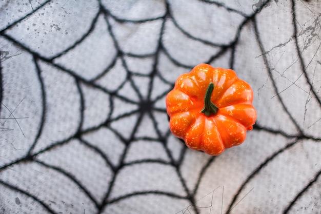 Halloween-pompoen op de achtergrond van de spinnewebtextuur.
