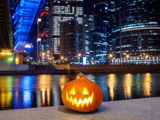 Halloween-pompoen op de achtergrond van wolkenkrabberlichten in de nachtstad