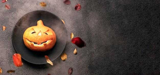 Halloween-pompoen op een zwarte plaat en een zwarte achtergrond. enge brandende ogen, een menu voor een bar of een briefkaartuitnodiging voor een vakantiekopieruimte.
