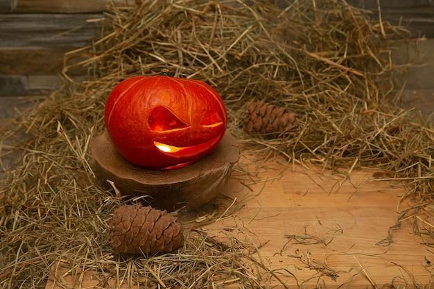Halloween-pompoen staat in hooi op een houten standaard in de buurt van boskegels