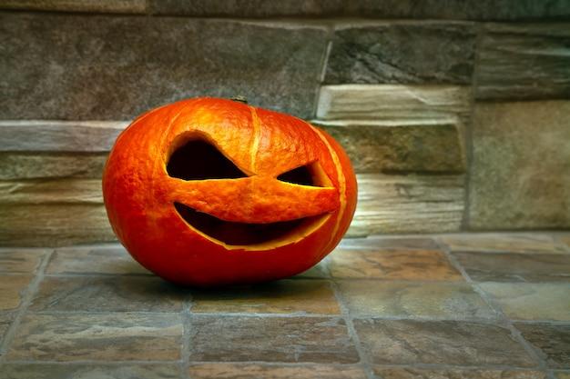 Halloween-pompoen staat op een groen tapijt tegen een stenen muur jack o lantern