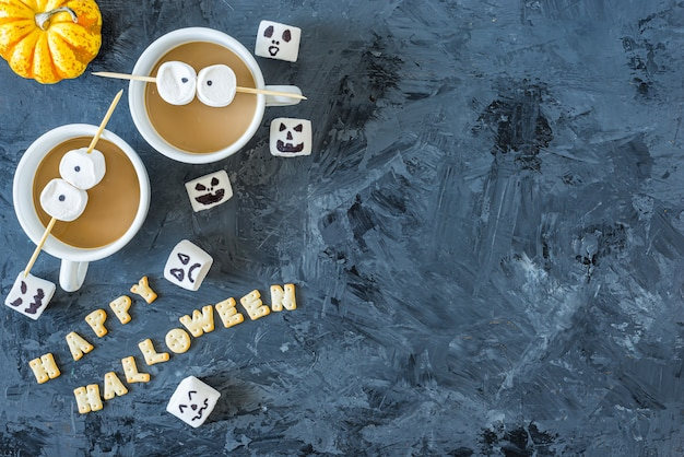 Halloween-pompoencupcakes met 2 koppen koffie en marshmallow-ogen, geserveerd op zwart, met vrolijke halloween-zin, bovenaanzicht, plat lag, copyspace
