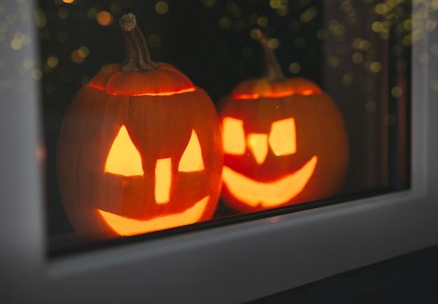 Halloween-pompoenen bij vensters met bokeh.