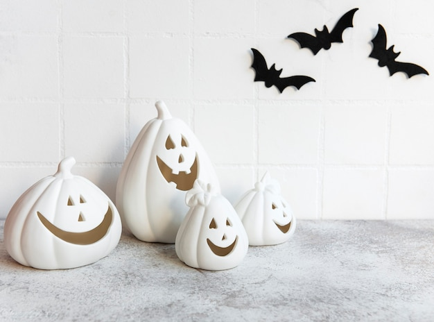 Halloween-pompoenen en jack o lantern decor tegen een witte muur met vleermuizen.