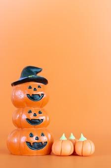 Halloween-pompoenen (jack-o'-lantern) op oranje achtergrond, hallo oktober-concept
