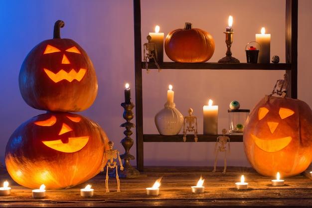Halloween-pompoenen met kaarsen op houten lijst