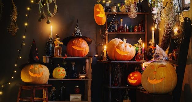 Halloween-pompoenen met lichtjes en brandende kaarsen en toverdrankjes in het huis van de heks