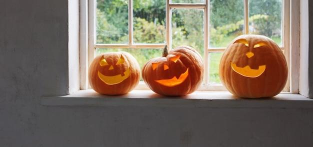 Halloween-pompoenen op witte vensterbank