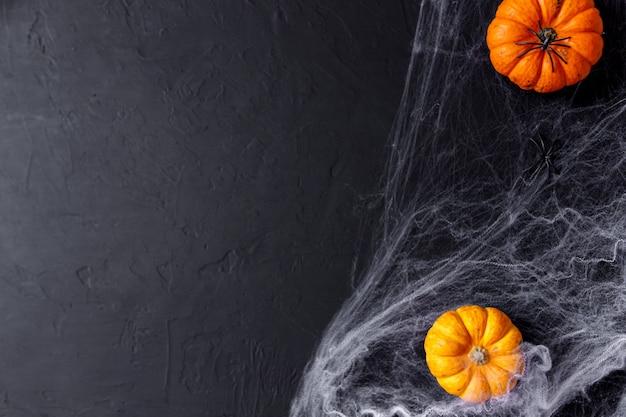 Halloween-pompoenen op zwarte achtergrond met griezelige spin en web.