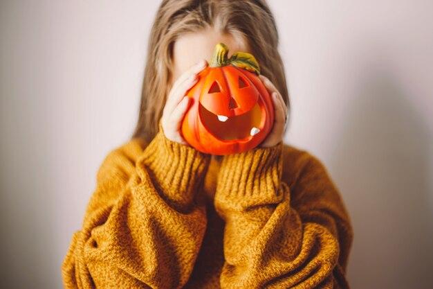 Halloween-pompoenlamp in de handen van een meisje bedekt haar gezicht