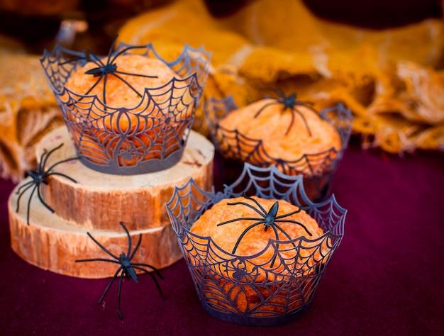 Halloween-pompoenmuffins versierd met spinnen en spinnenweb