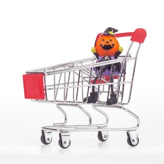 Halloween-pompoenspeelgoed in boodschappenwagentje op wit