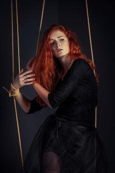Halloween roodharige vrouw marionet pop gebonden met touwen. meisjespop met kabels met handen en voeten wordt gebonden die