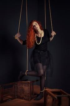 Halloween roodharige vrouw marionetpop vastgebonden met touwen. meisjespop vastgebonden met touwen met handen en voeten