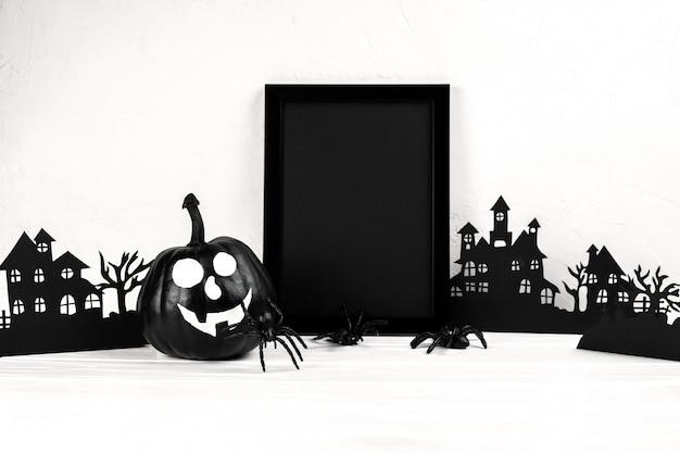 Halloween-samenstelling. zwart fotolijst en papier kunst verlaten dorp, pompoen op wit.