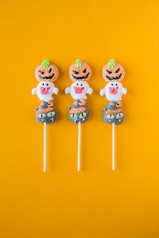 Halloween-snoepjes gerangschikt in een afwisselend patroon op een gekleurde achtergrond