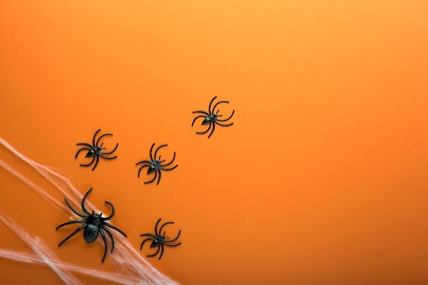 Halloween spinnenweb en spinnen als symbolen van halloween op oranje achtergrond
