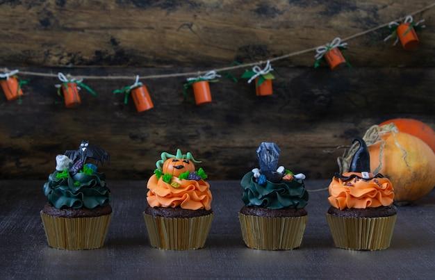 Halloween-symbolen, voorbereiding op de vakantie. oranje pompoen cupcakes en houten decor