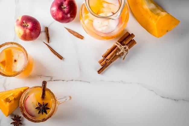 Halloween, thanksgiving. traditionele herfst, winterdranken en cocktails. pittige hete pompoensangria, met appel, kaneel, anijs. op een witte marmeren tafel, in glazen mokken. bovenaanzicht kopie ruimte