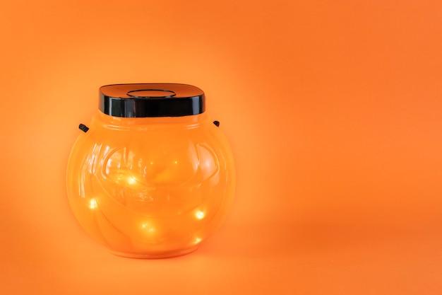 Halloween trick or treat bowl met lampjes op oranje achtergrond