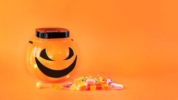 Halloween trick or treat bowl met snoepjes op oranje achtergrond
