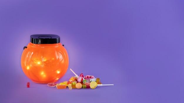 Halloween trick or treat bowl met snoepjes op paarse achtergrond