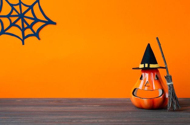 Halloween vakantie achtergrond met jack lantaarns pompoen bezem en heks hoed op houten tafel