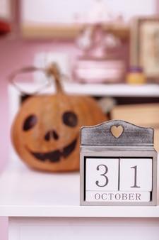Halloween-vakantie met pompoen en kalender met oktober op houten tafel in de kamer van schoolmeisjes