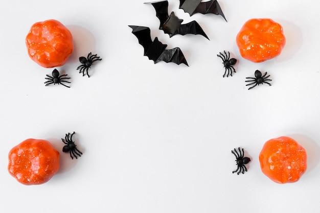 Halloween-vakantie. plat op een witte achtergrond. pompoenen, vleermuizen en spinnen. kopieerruimte. ansichtkaart met lijst