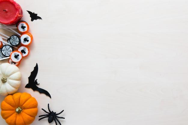 Halloween-vakantieachtergrond met spinnen, knuppels, suikergoed en pompoenen op hout
