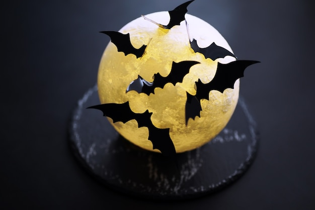 Halloween-vakantieconcept. oude stenen tafel in de vorm van vleermuizen. halloween papieren versieringen op donkere achtergrond. maan speelgoed.