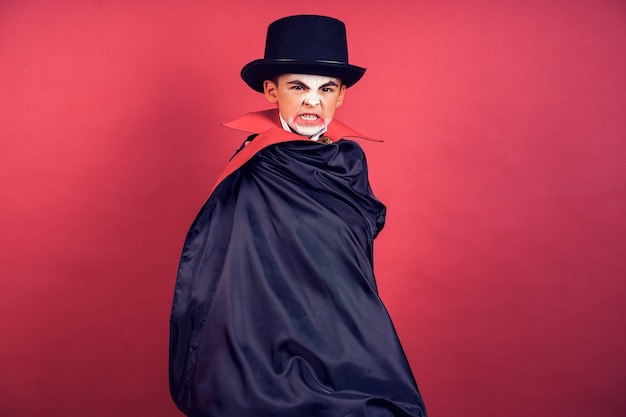 Halloween-vampierjongen zwaait met zijn zwarte, rode mantel met zijn handen omringd op rode studioachtergrond. kid vampiermake-up.