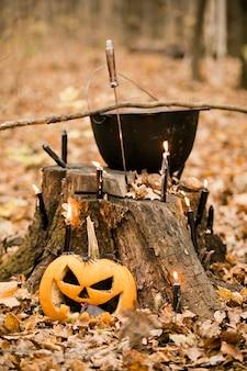 Halloween-versieringen in het bos: ketel, pompoen, kaarsen en dolk. drie vintage heksen voeren een magisch ritueel uit