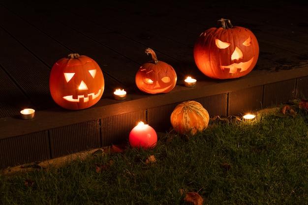 Halloween-voorbereiding, pompoenen met kaarsen erin die oplichten in het donker