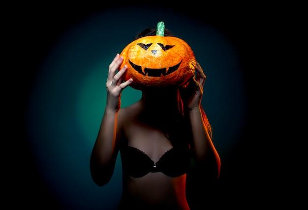 Halloween, vrouw in ondergoed met pompoen