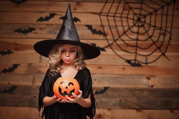 Halloween witch-concept - een klein kaukasisch heksenkind dat teleurstelt zonder snoep in de pot van de halloween-snoeppompoen over vleermuis en spinnenweb achtergrond.