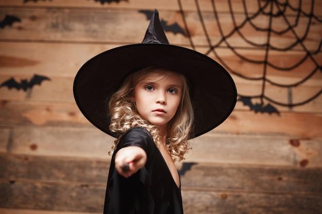 Halloween witch concept - kleine heks kind genieten van spelen met toverstaf. over vleermuis en spinnenweb achtergrond.