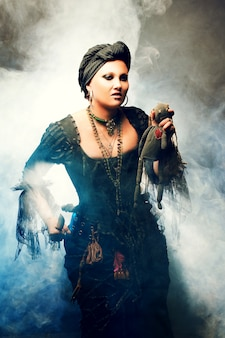 Halloween witch creëert magie. vrouw in heksen kostuum met voodoo-pop in de hand