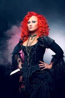 Halloween witch creëert magie. vrouw met rood haar in heksenkostuum